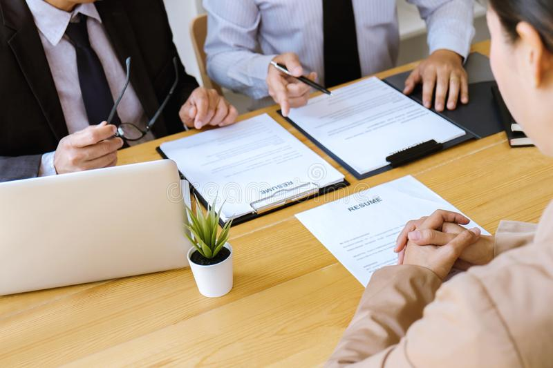 Two selection committee manager reading a resume during a job interview, Employer interviewing to ask young female job seeker for. Recruitment talking in office royalty free stock photos