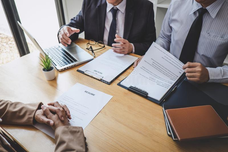 Two selection committee manager reading a resume during a job interview, Employer interviewing to ask young female job seeker for. Recruitment talking in office royalty free stock photography