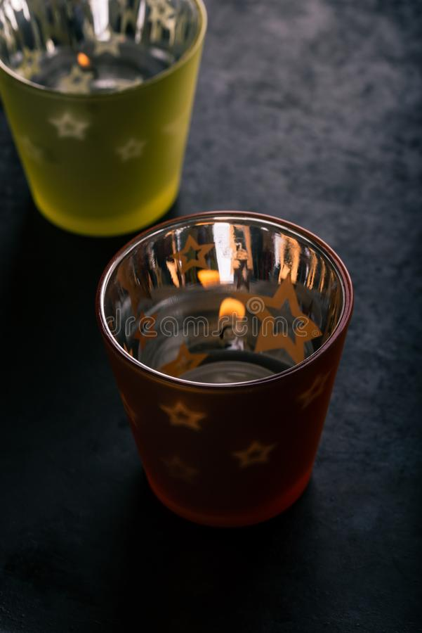 Two semi transparent cups with candle inside. Vertical photo of two color semi-transparent cups with shiny surface from inside. Transparent stars are on side royalty free stock image