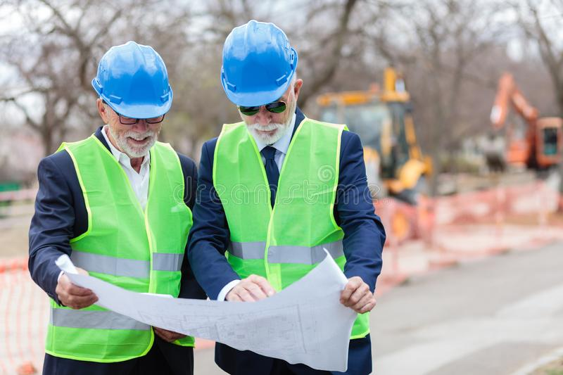 Two senior architects or business partners working on a construction site during inspection, looking at blueprints stock photo