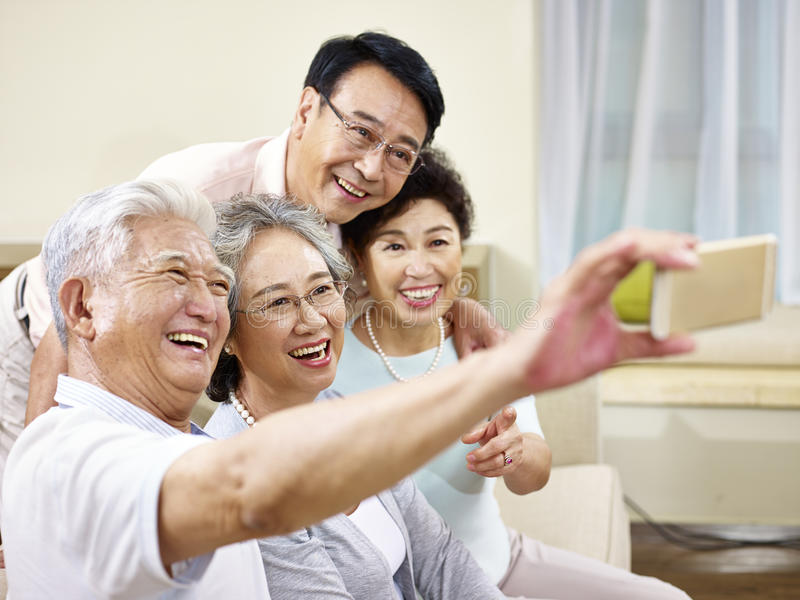 Two senior asian couples taking a selfie royalty free stock images