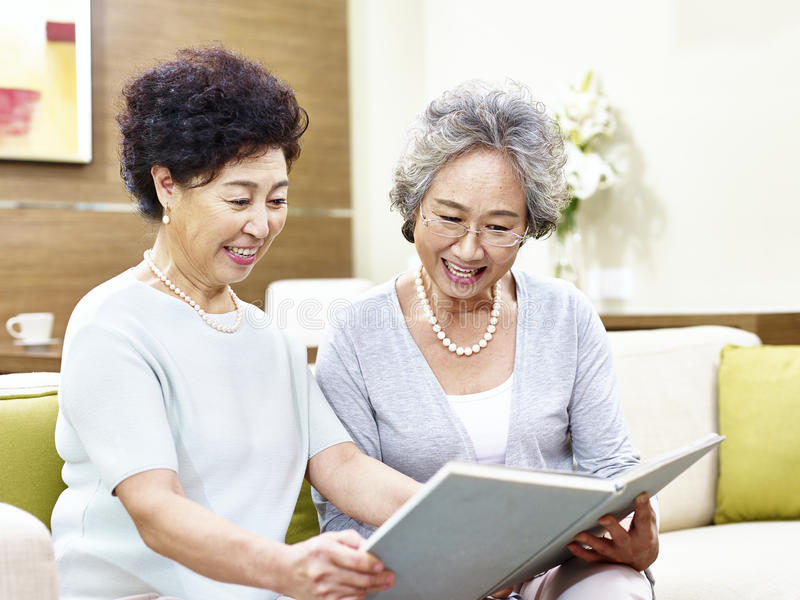 Two senior asian women reading a book together stock photo