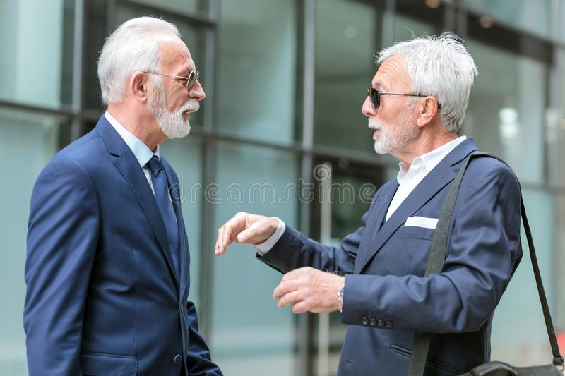 Two senior businessmen with gray hair and beard meeting and discussing in front of an office building. View from the side. Active stock image