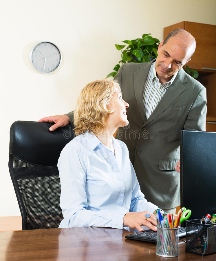 Two senior colleagues in office. Two smiling elderly colleagues working in office stock images
