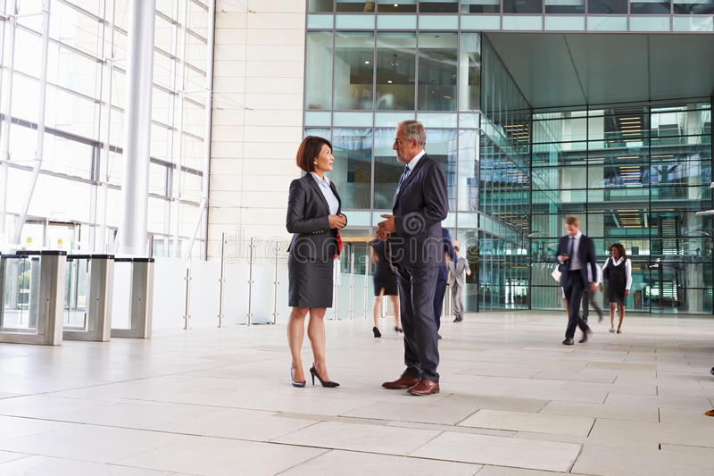 Two senior colleagues talking in the foyer of a big business royalty free stock photo