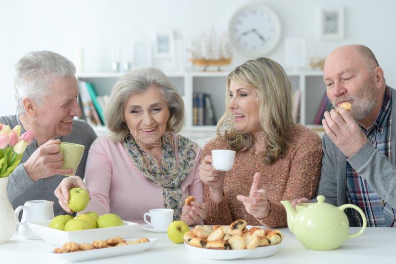 Two Senior couples drinking tea stock image