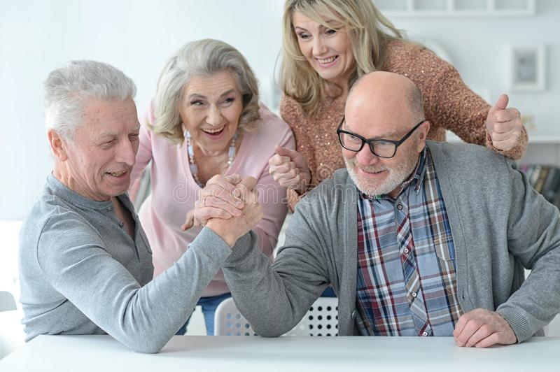 Senior couples using laptop. Two senior couples having fun together while sitting at table stock photography