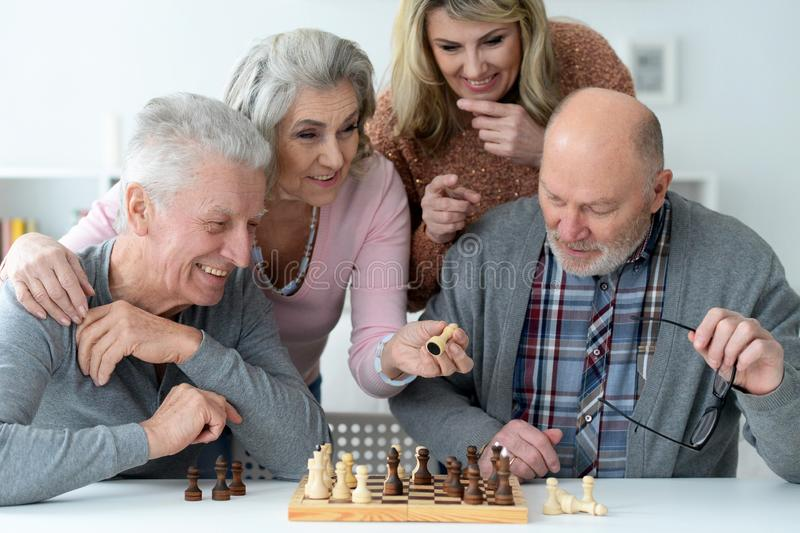 Close up portrait of two senior couples sitting at table royalty free stock photography