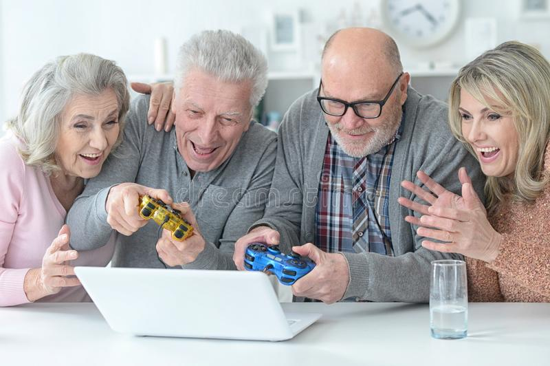 Two senior couples using laptop at home stock photography