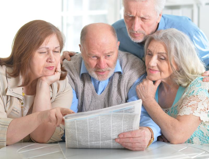 Senior couples reading newspaper. Two senior couples sitting at table and reading newspaper royalty free stock images