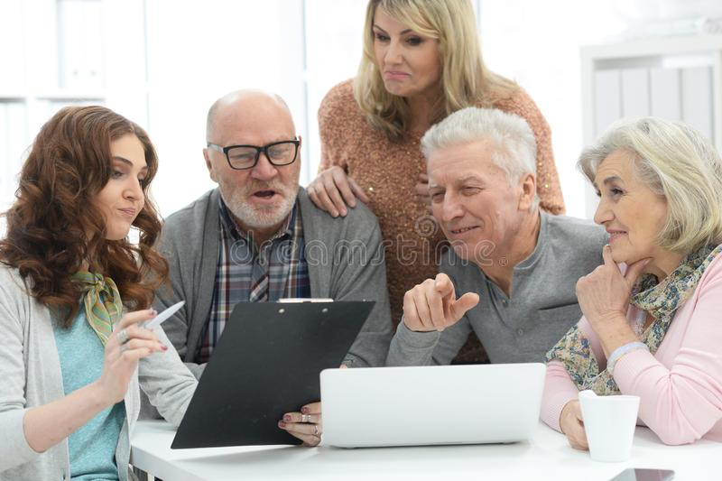 Two senior couples talking with consultant while sitting at table. And looking at laptop royalty free stock photo