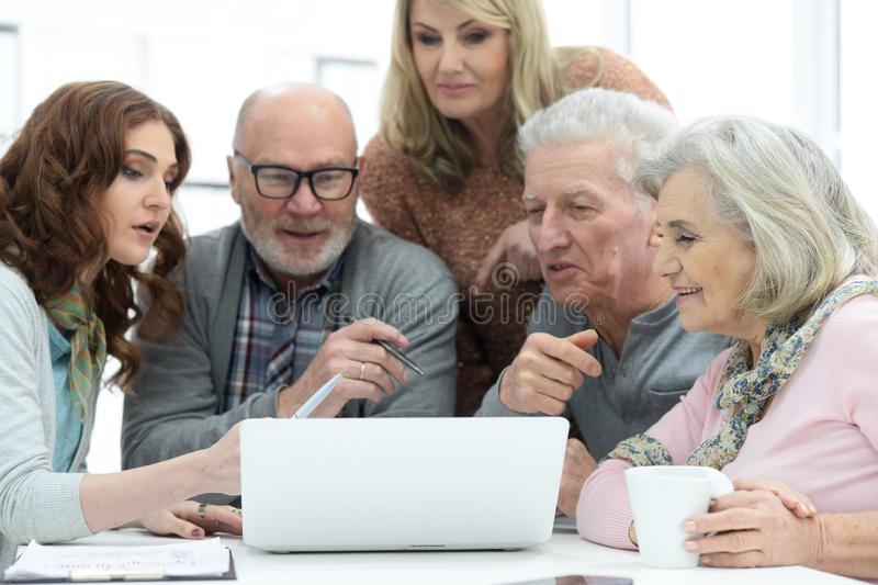 Two senior couples talking with consultant while sitting at table. And looking at laptop stock photos