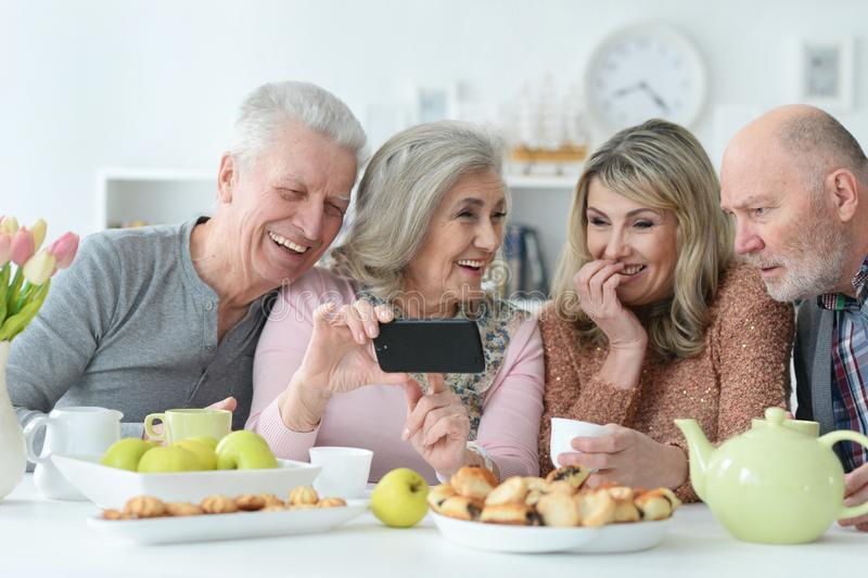 Two senior couples using smartphone during morning tea royalty free stock photography