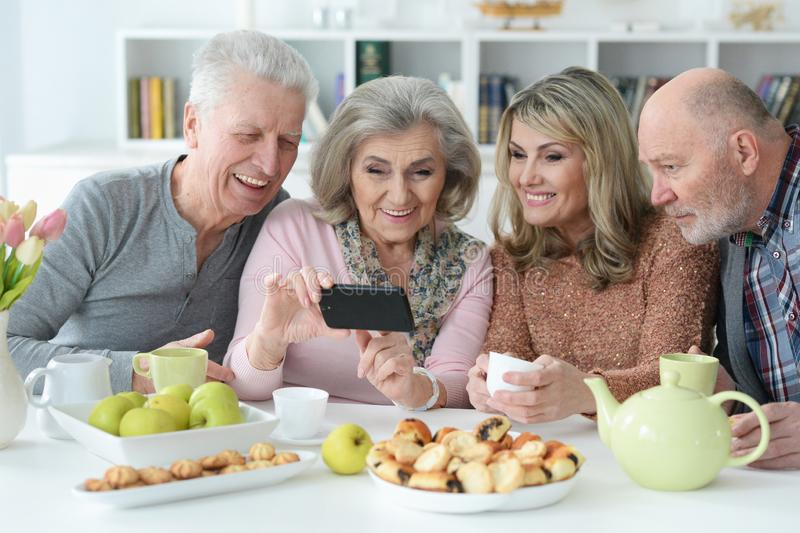 Two senior couples using smartphone during morning tea stock photo