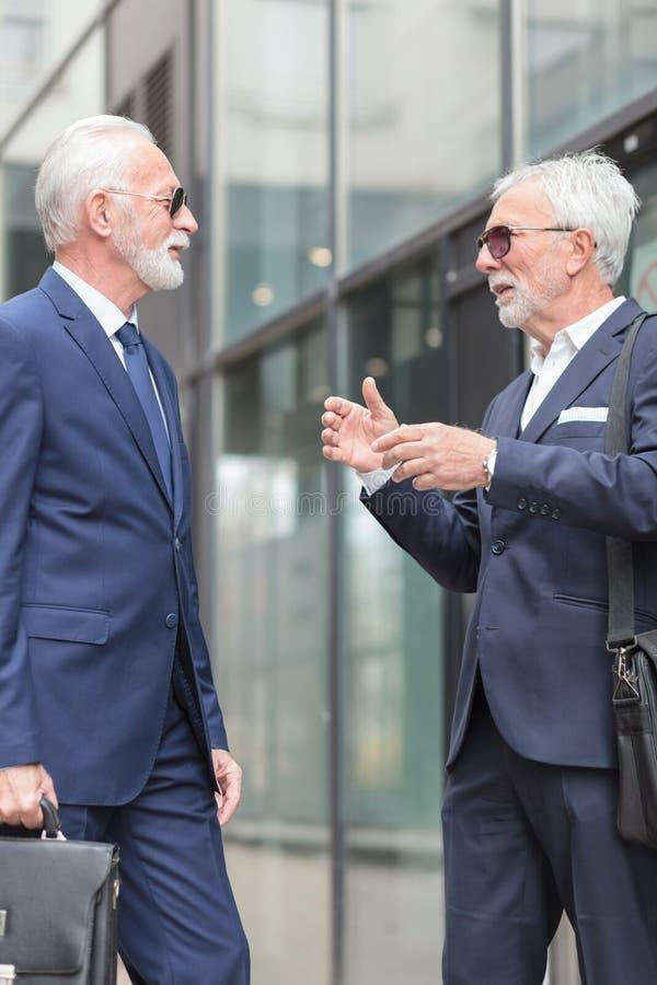 Two senior gray hair businessmen talking in the street. Two senior gray hair businessmen standing in the street and talking. Surrounded by tall office buildings stock image