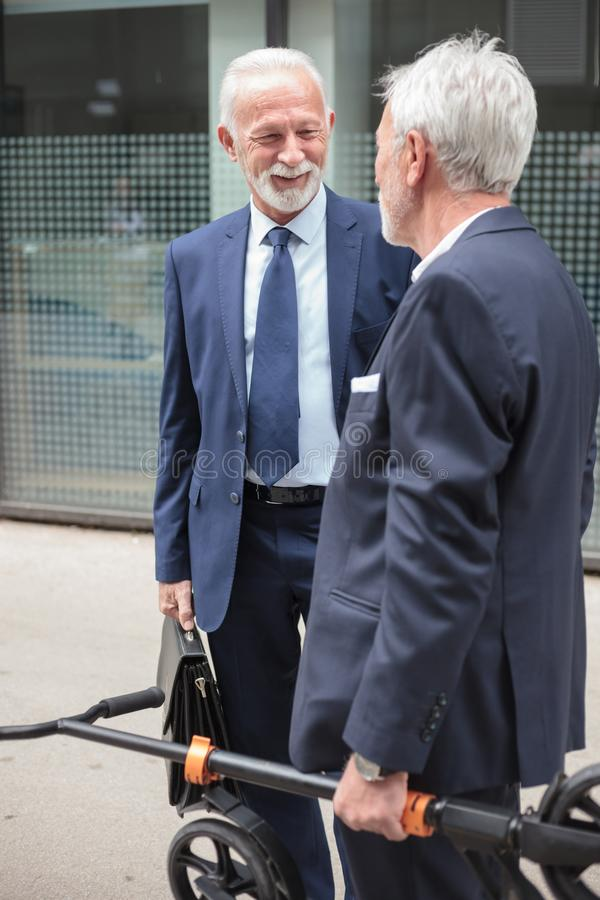 Two senior gray haired businessmen talking on the sidewalk. In front of an office building. One men is carrying a kick scooter for commuting. Finance and stock photo