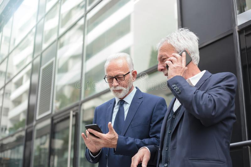 Two happy senior businessmen using smart phones, talking and messaging. Two senior gray haired businessmen using smart phones, talking and messaging, standing on royalty free stock photography
