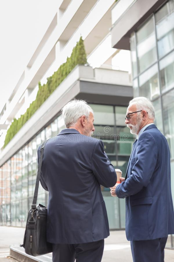 Two senior gray haired businessmen walking down the street and talking, rear view stock photo