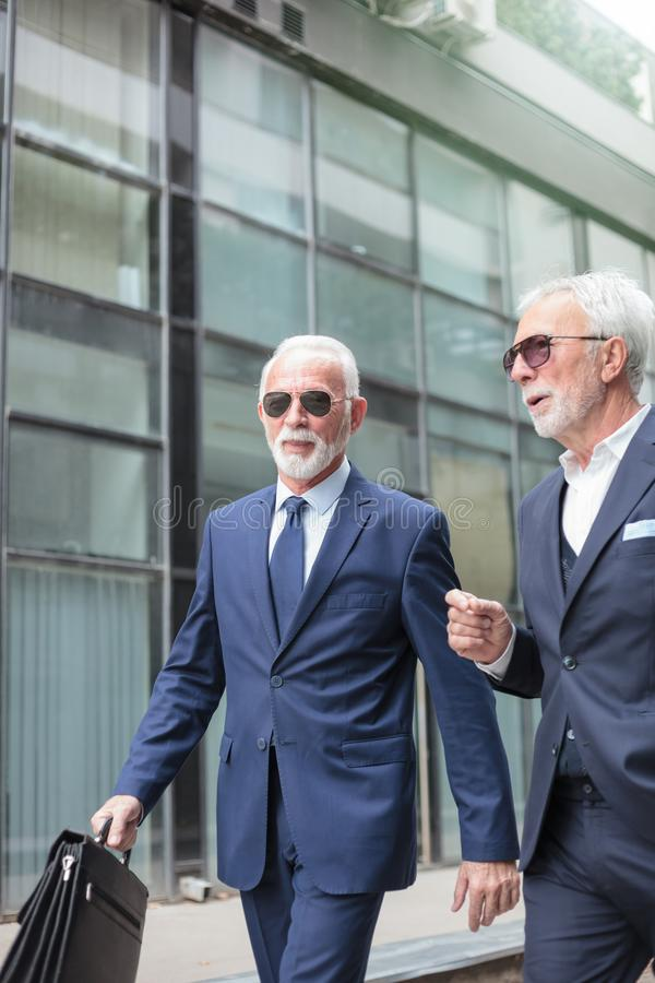 Two senior businessmen walking on a sidewalk in front of office building. Two senior gray haired businessmen walking on a sidewalk in front of a glass facade royalty free stock photo