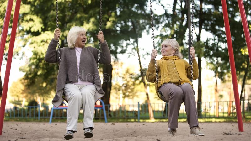 Two senior ladies enjoying ride on swings in park, elderly friends, retirement stock photo