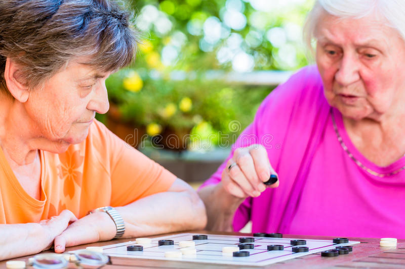 Two senior ladies playing board game in rest home stock images