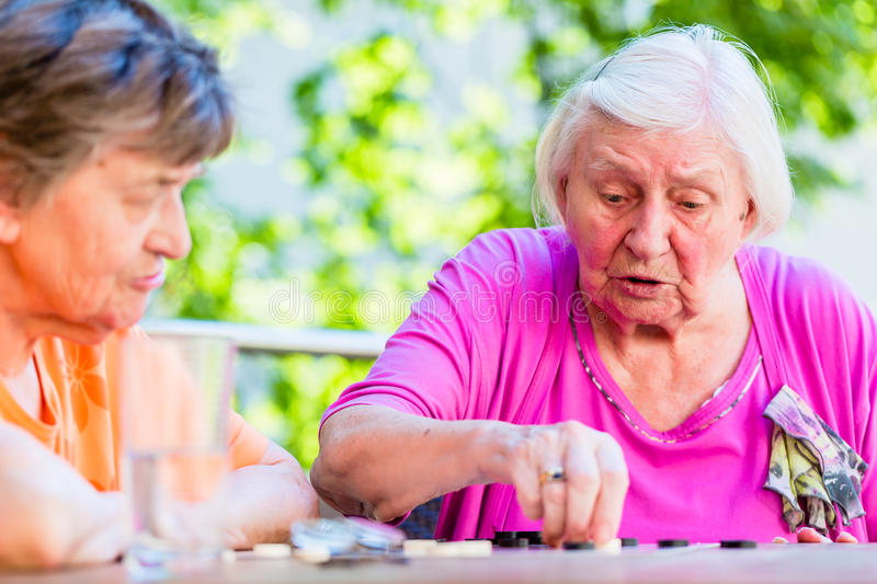Two senior ladies playing board game in rest home royalty free stock photography