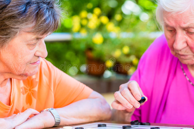 Two senior ladies playing board game in rest home royalty free stock photo