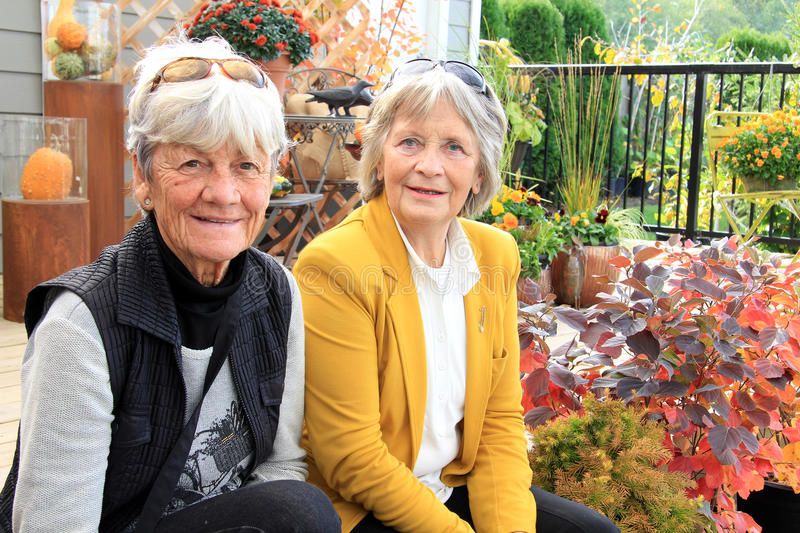 Two senior ladies seated on a patio. Two senior ladies, age 76, seated outside on a wood deck during autumn stock images