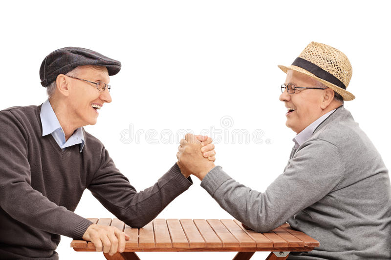 Two senior man having an arm wrestle competition. Two senior men having an arm wrestle competition seated at a table isolated on white background stock photography