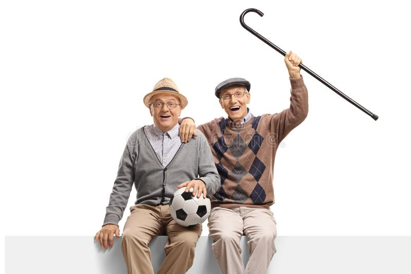 Two senior men with a football seated on a panel royalty free stock image