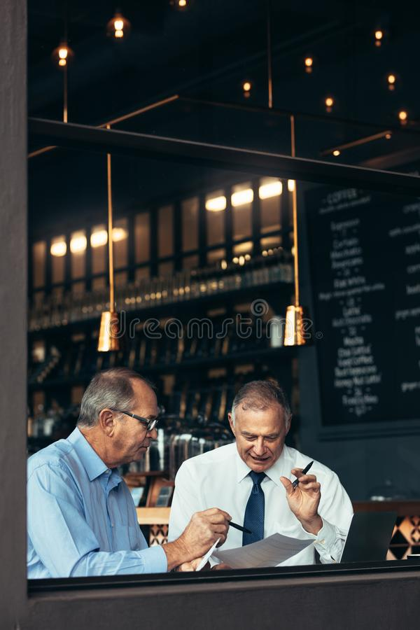 Two senior men having business meeting in a pub royalty free stock image