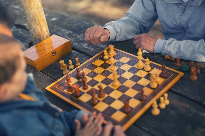 Two senior men having fun and playing chess at park. Active retired people old friends and free time two senior men having fun and playing chess at park spend royalty free stock image