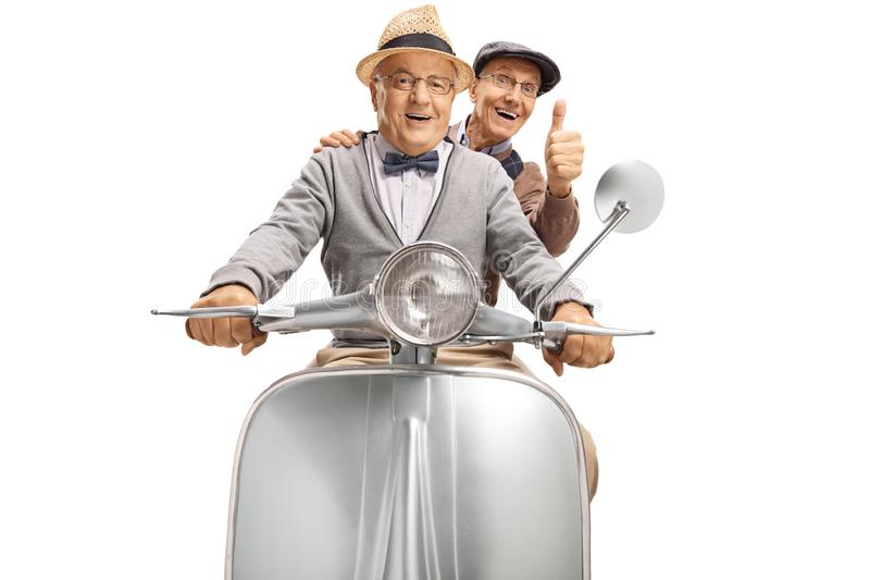 Two senior men riding on a vintage scooter and showing thumbs up. Isolated on white background stock photography