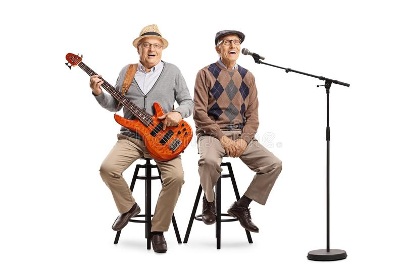 Two senior men sitting with an electric guitar and a microphone stock photo