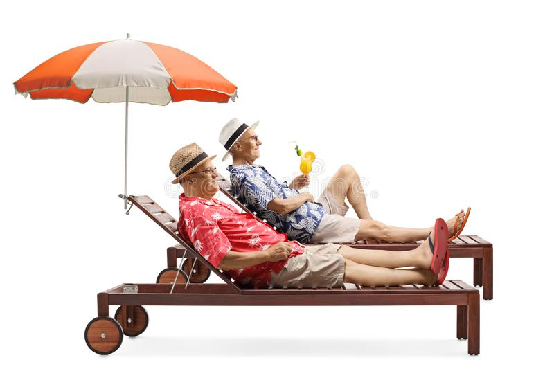 Two senior men on vacation enjoying a cocktail on a sunbed under umbrella stock image