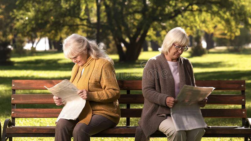 Two senior offended female friends reading newspapers, sitting on bench in park royalty free stock images