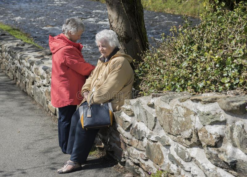 Two senior woman chatting outdoors stock images