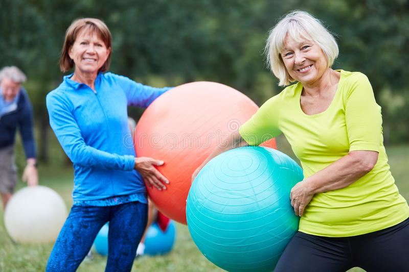 Two senior women with exercise ball. In a rehab back course in the park stock image