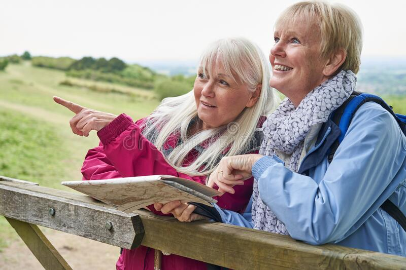 Two Senior Women Friends On Walking Holiday Resting On Gate With Map stock images