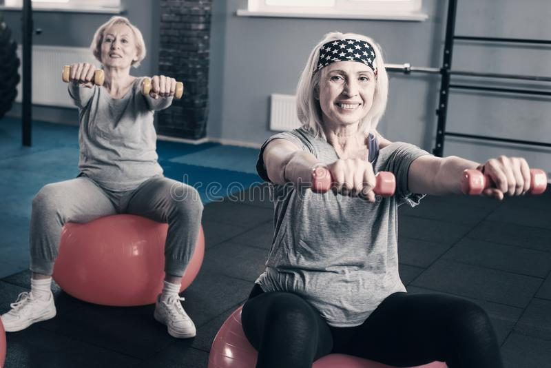 Two senior women stretching out hands with dumbbells stock image