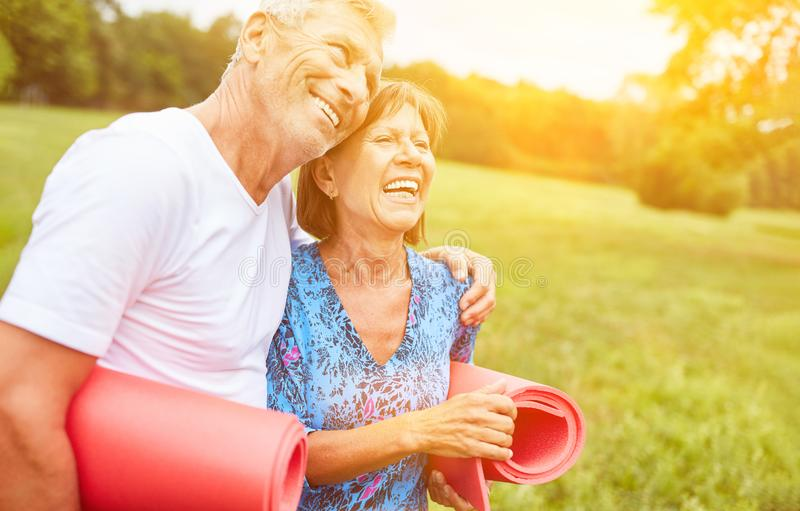 Two seniors as a couple with gymnastics mat. In nature stock image