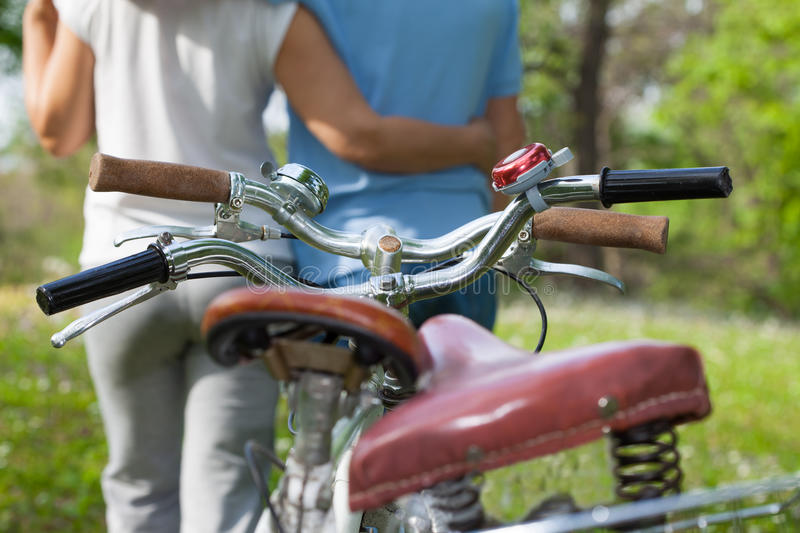 Two seniors with bicycles. Two embraced seniors with bicycles in the park royalty free stock photos