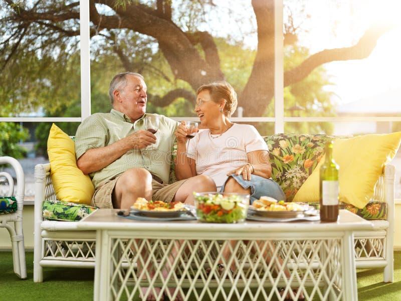 Two seniors having dinner on patio. stock photos