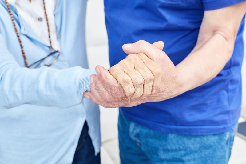 Two seniors hold hands stock images