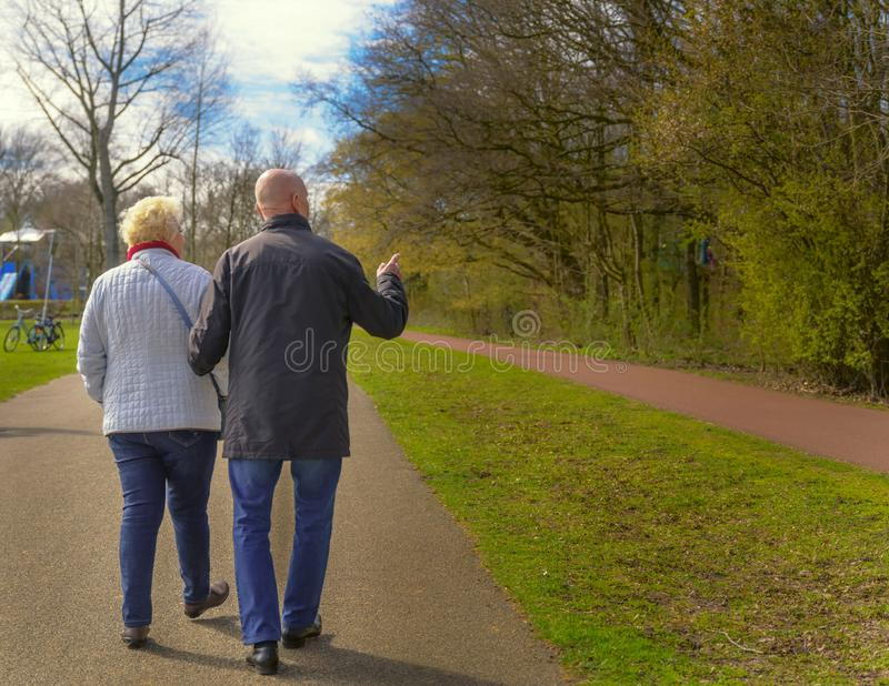 Two seniors walking in spring park. Spring time stock photography