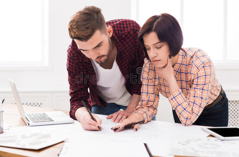 Two serious architects discussing building plan stock photos