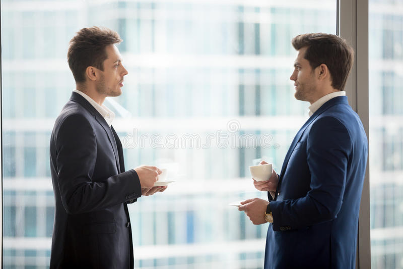 Two serious businessmen drinking coffee and talking near big win royalty free stock photos