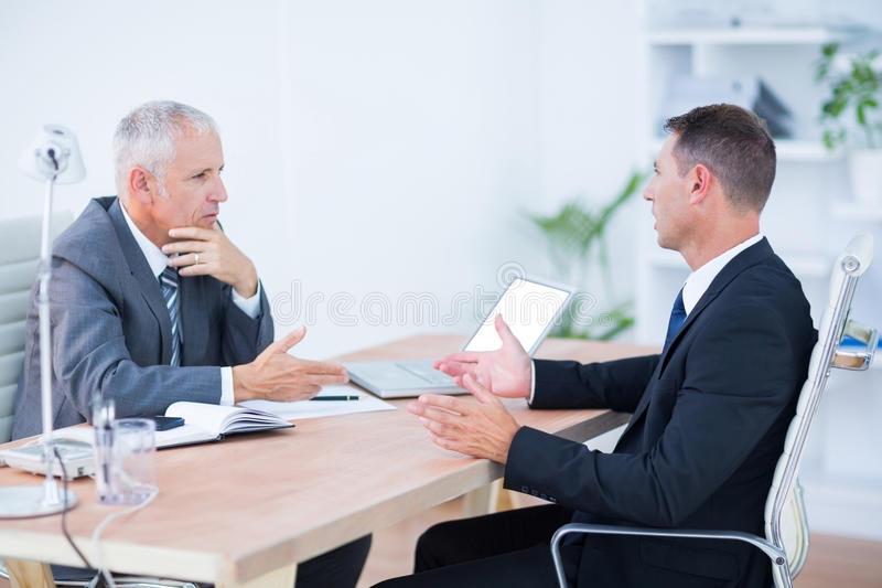 Two serious businessmen speaking and working stock image