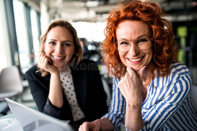 Two female business people sitting in an office, talking. royalty free stock photo