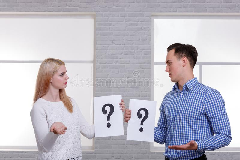 Two serious people, a guy and a girl, are holding a leaf with a question mark and looking at each other with reparation. Two serious people, a guy and a girl of stock photo
